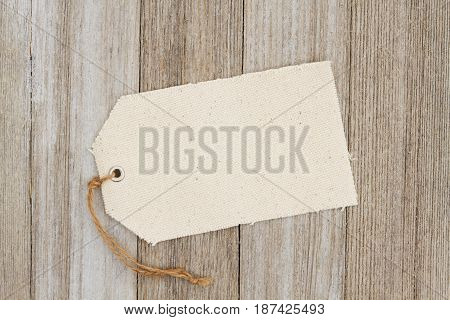 A cloth gift tag on weathered wood that is blank for your message