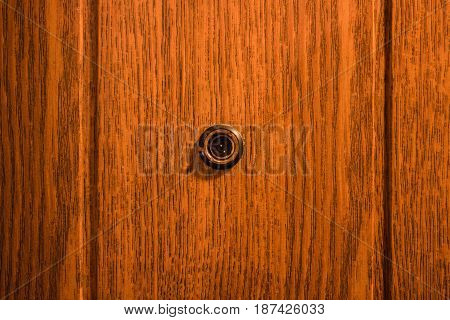 A peephole in the entrance door of a brown color