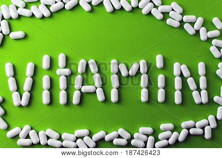 text - vitamins - of white pills, tablets on a green background, around pilule
