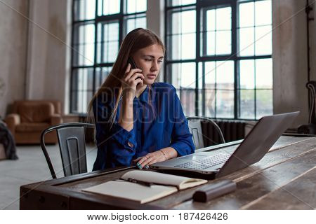Businessman talking on the phone while working on laptop sitting at her desk in stylish modern office.