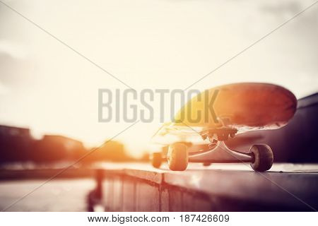 Skateboard stands on a sunset background, close-up, top and side view. Concept active recreation, advertising.
