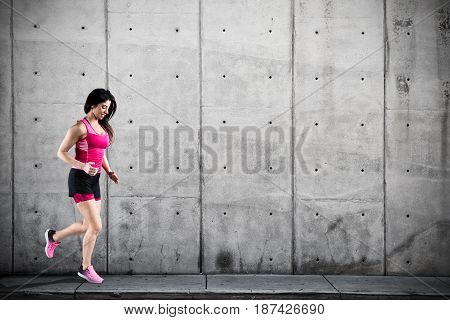 Athletic woman runner in sportswear on the asphalt of a road