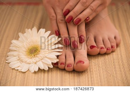 Closeup photo of a female feet and hands at spa salon on pedicure and manicure procedure