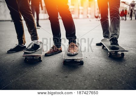 Group of friends skateboarders rest on the street and skateboard. Concept active rest with friends outdoors in summer. Monochrome and high contrast.
