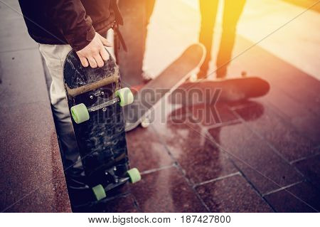 Male skateboarder man holds a skate board in his hand against the background of a team of team friends and a sunset. Concept of engaging in active and extreme sports.