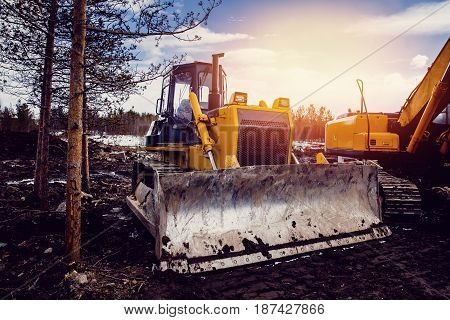 Yellow excavator on new construction site, with the bright sun and nice blue sky in the background. Concept of road and house construction