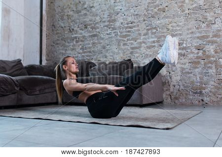 Female athlete doing static abs v hold exercise strengthening core muscles on floor in loft studio.