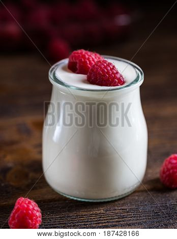 White yogurt with raspberries in glass bowl on rustic table.