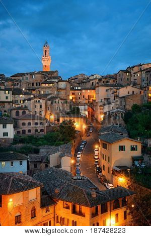 Medieval town Siena skyline view with historic buildings in Italy at night