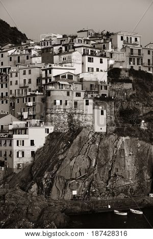 Manarola overlook Mediterranean Sea with buildings over cliff in Cinque Terre, Italy. Black and white.