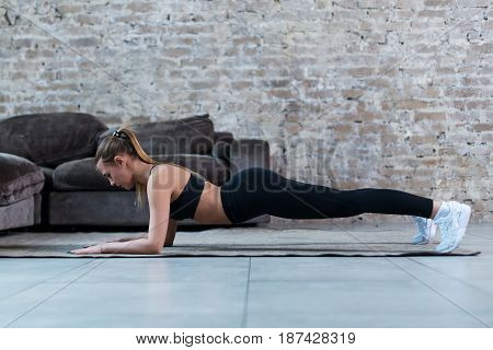 Side view of slim female athlete standing in plank position on floor strengthening core muscles indoors.