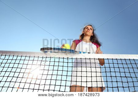 woman tennis player with racket and ball standing in front of the net