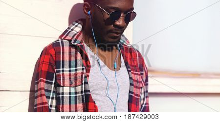 Fashion Portrait Young African Man Listens To Music In Headphones, Hipster Wearing A Plaid Red Shirt