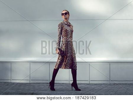 Fashion Woman Model Wearing A Leopard Dress Is Walking In A Evening City