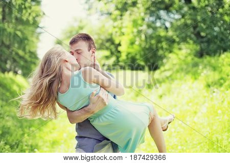Happy young sweet couple is kissing man and woman in love he holds her on a hands at grass outdoors