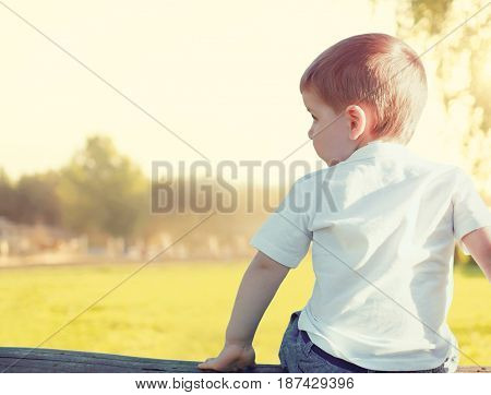 Little child boy is sitting pensive looking away outdoors over a sunset landscape view from back