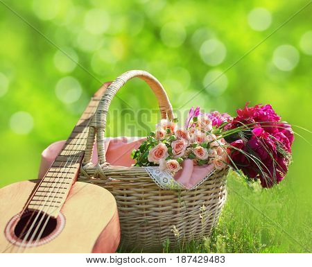 Romance, Love, Valentine's Day Concept - Wicker Basket With Bouquet Of Flowers, Guitar On The Grass.