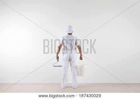Rear view of painter man looking at blank wall with paint roller and bucket isolated on white room