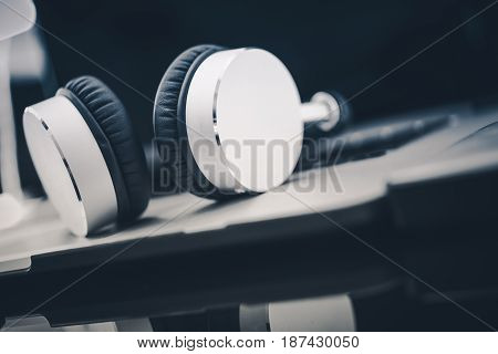 Listening Audiobooks Concept with Large Wireless Headphones on the Laptop Computer Closeup.