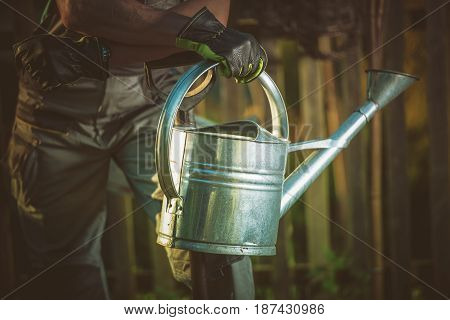 Watering Can Gardening Concept Photo. Gardner with Vintage Styled Metallic Garden Watering Can.