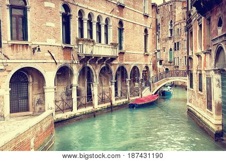 Canal with gondolas in Venice Italy, photo filters applied