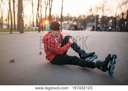 Roller skater sitting on asphalt in city park