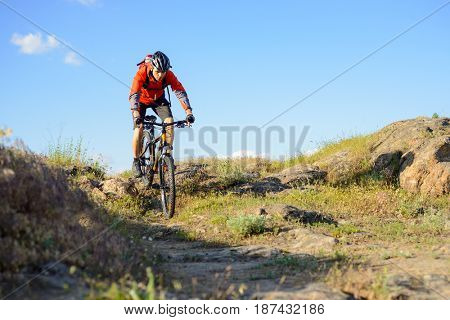 Cyclist in Red Jacket Riding the Mountain Bike on the Beautiful Spring Rocky Trail. Extreme Sport Concept