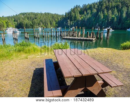 Picnic table at the shore of the bay with moored boats