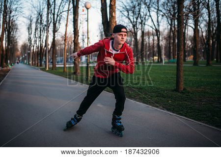 Roller skater rides by sidewalk in city park