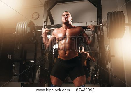 Weightlifter exercise with barbell in sport gym