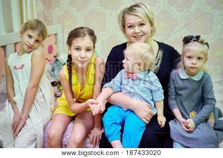 Smiling woman and four children sit on couch in room.