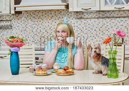 Plump woman sits eating homemade baked sweets at table in kitchen, little dog near on table.
