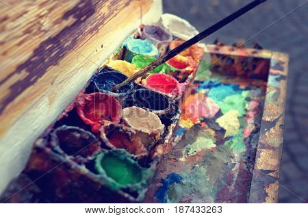 Artist at work. The workplace of the artist brushes paints and canvas. Multicolor oil paints on a palette close up.