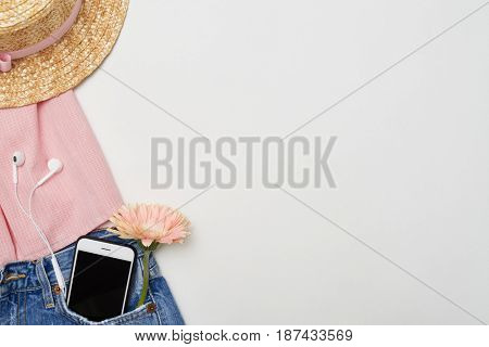 Top view of assorted fashionable clothes on white desktop. Basic summer feminine outfit with accessories