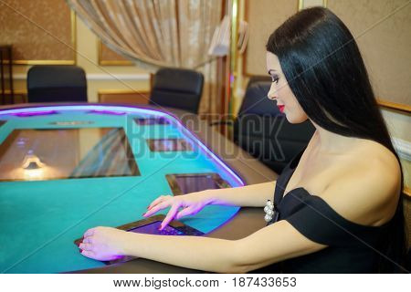 Pretty young woman in black dress with red lips plays poker in casino at electronic table