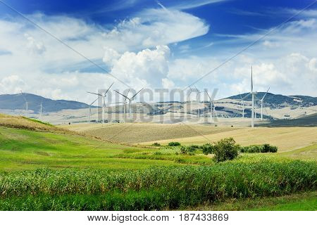 Wind generator turbine and blue sky with clouds - ecology energy saving concept