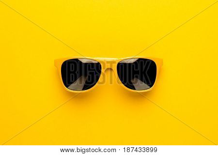 studio shot of yellow sunglasses. summer is coming concept with yellow sunglasses. sunglasses on yellow background. sunglasses on seamless background. top view of sunglasses