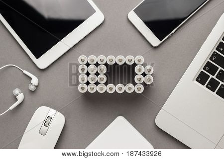 conceptual image of battery charge level pictogram made of rechargeable batteries with some mobile devices that use battery accumulators like smart phone, tablet computer, laptop and power bank. battery concept over grey background