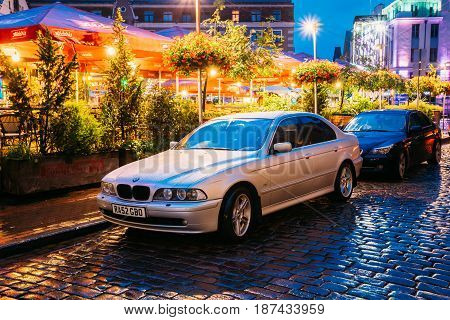 Riga, Latvia - July 3, 2016: Sedan Car BMW 5 Series E39 Parking Near Street Cafe In Evening Or Night Illumination In Old Town On Kalku Street