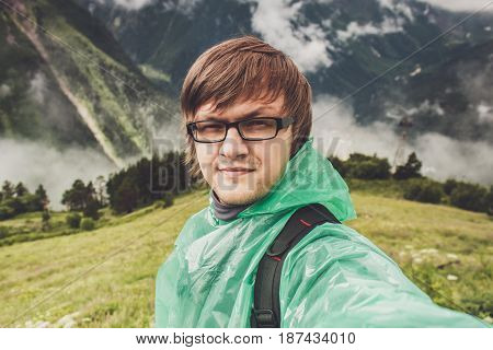 man in glasses taking selfie. mountains with green grass in background