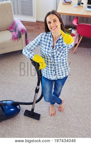 Overhead shot of charming girl holding vacuum cleaner and showing clearness of carpet