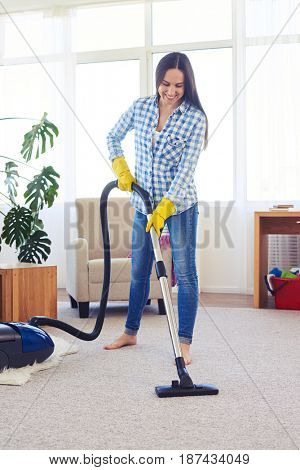 Mid shot of beautiful charwoman cleaning with vacuum cleaner carpet