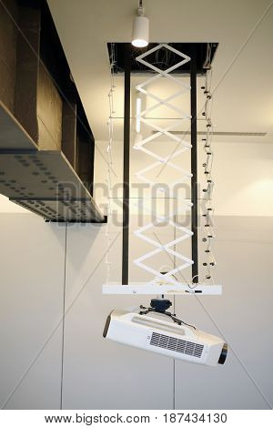 White modern projector for presentation hangs from ceiling in hall