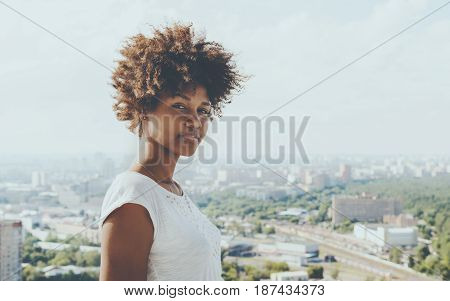 Cute young afro american girl with modern summer cityscape in background attractive black curly lady with on high observation point with copy space zone for message your logo text or advertising
