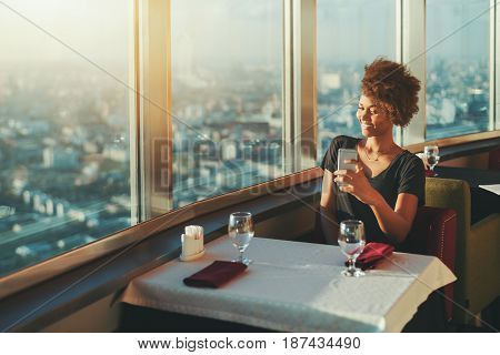 Attractive mixed curly woman making selfie on her smartphone while waiting her friend in cafe on roof charming laughing black lady photo messaging with her family while sitting in luxury restaurant