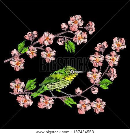 Embroidery Japanese bird sitting on the sakura branch isolated on black background.