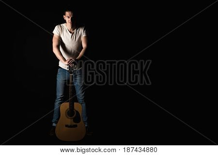 Guitarist, Music. A Young Man Stands With An Acoustic Guitar, On A Black Isolated Background. Horizo