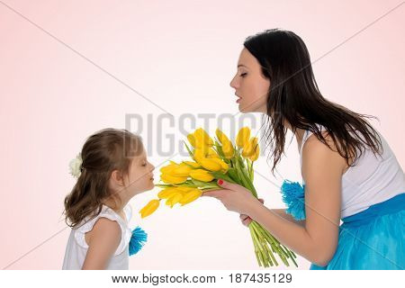 Beautiful young mother and little daughter in the same blue long skirts tutus , standing sideways to the camera , admiring the bouquet of yellow tulips.Little girl enjoying the smell of flowers.