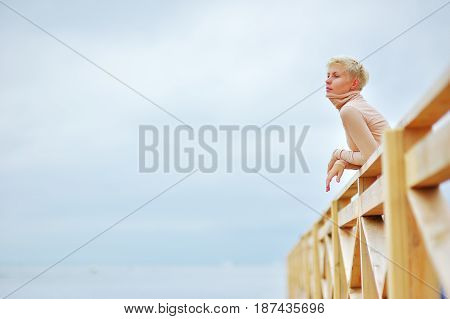 Portrait of young beautiful girl blonde standing on the wooden deck contemplating and enjoying the fresh air on grey-blue background of the sky.