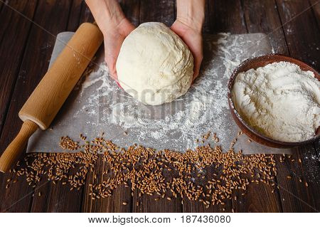 Woman's hands knead dough on a table
